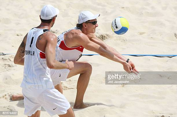 Peter Gartmayer of Austria goes to return the ball alongside Clemens Doppler of Austria as they take on Renato Gomes and Jorge Terceiro of Georgia in...