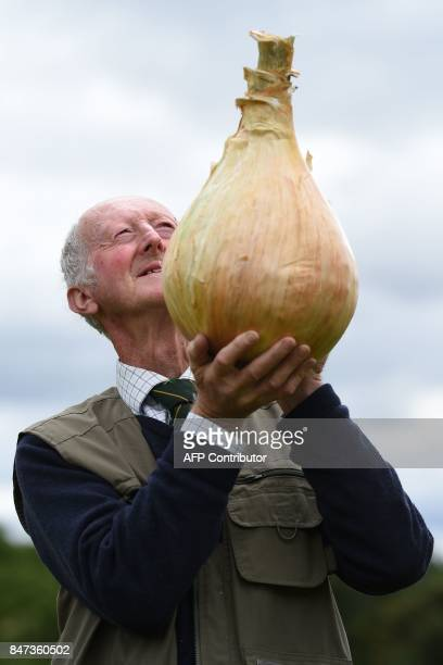 Peter Glazebrook poses for a photograph with his 6.6 kg onion which won its class in the giant vegetable competition on the first day of the...