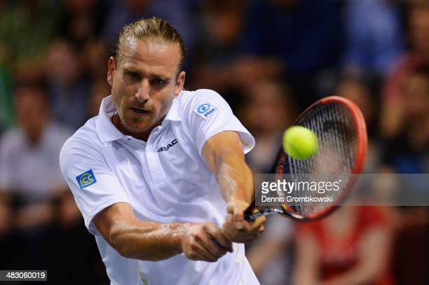 Peter Gojowczyk of Germany plays a backhand in his match against Gael Monfils of France during day 3 of the Davis Cup Quarter Final match between...
