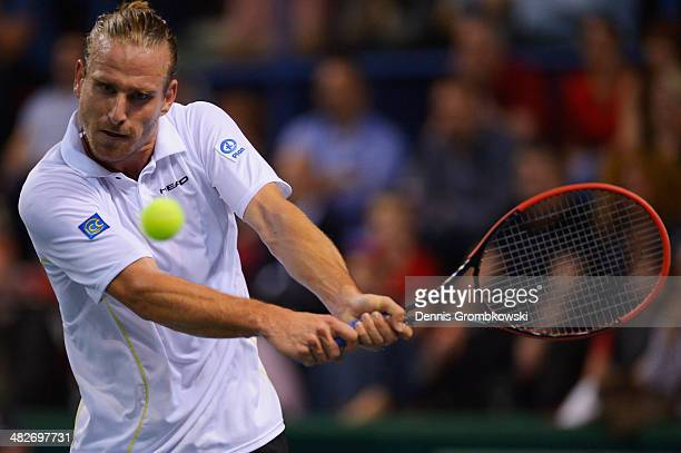 Peter Gojowzyk of Germany plays a backhand in his match against Jo-Wilfried Tsonga of France during day 1 of the Davis Cup Quarter Final match...