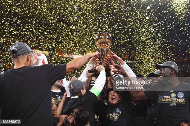 Peter Guber of the Golden State Warriors holds ups the Larry O'Brien Trophy and celebrates with his team after winning Game Five of the 2017 NBA...