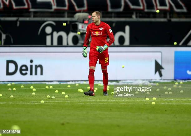 Peter Gulacsi goalkeeper of Leipzig picks up tennis balls from the field during the Bundesliga match between Eintracht Frankfurt and RB Leipzig at...