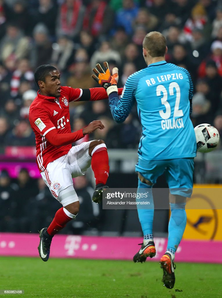 Peter Gulacsi of RB Leipzig (R) fouls Douglas Costa of Bayern Muenchen (L) and a penalty is awarded which is later score by Robert Lewandowski of Bayern Muenchen (not pictured) during the Bundesliga match between Bayern Muenchen and RB Leipzig at Allianz Arena on December 21, 2016 in Munich, Germany.