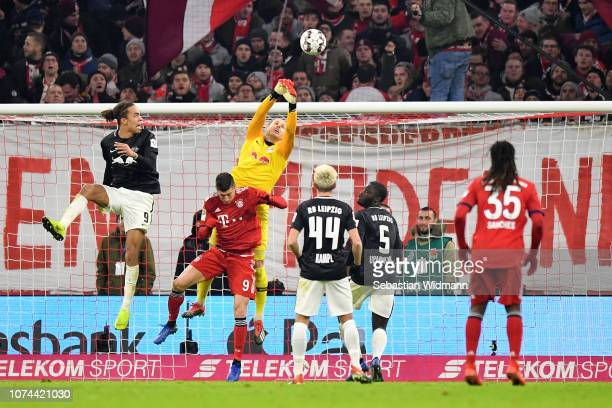 Peter Gulacsi of RB Leipzig punches the ball away from Robert Lewandowski of Bayern Munich during the Bundesliga match between FC Bayern Muenchen and...