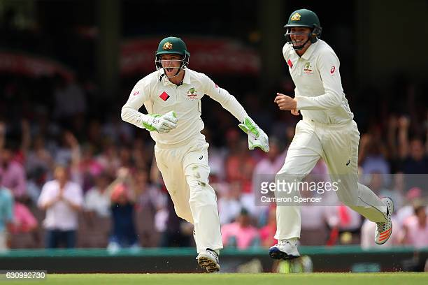 Peter Handscomb of Australia celebrates with team mate Matt Renshaw of Australia after running out Azhar Ali of Pakistan off a delivery by Nathan...