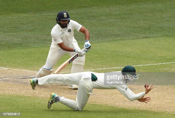 Peter Handscomb of Australia takes a catch to dismiss Rohit Sharma of India off the bowling of Nathan Lyon of Australia during day four of the First...