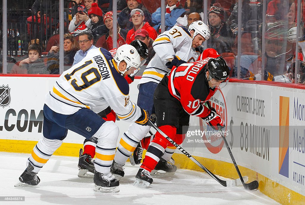 Peter Harrold #10 of the New Jersey Devils in action against Matt Ellis #37 and Cody Hodgson #19 of the Buffalo Sabres at the Prudential Center on February 17, 2015 in Newark, New Jersey. The Devils defeated the Sabres 2-1 after a shootout.
