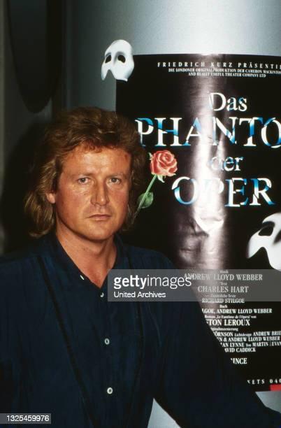 """Peter Hofmann, deutscher Tenor, vor dem Plakat zum Musical """"Das Phantom der Oper"""" in Hamburg, Deutschland um 1990."""