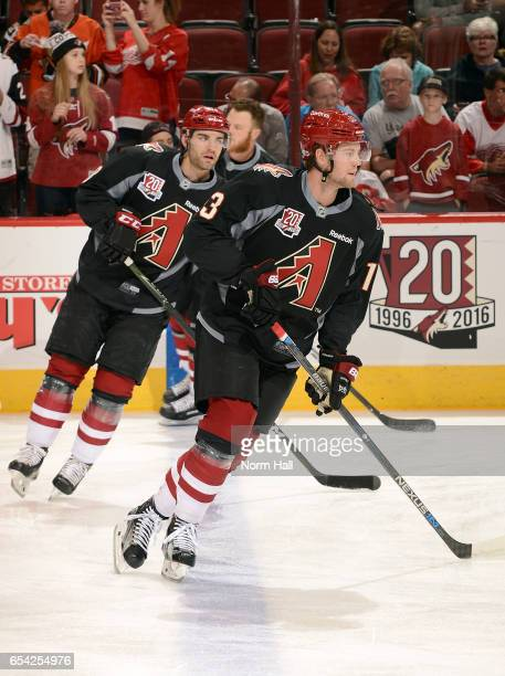 Peter Holland and Jordan Martinook of the Arizona Coyotes wear special Arizona Diamondbacks warm up jerseys before a game against the Detroit Red...