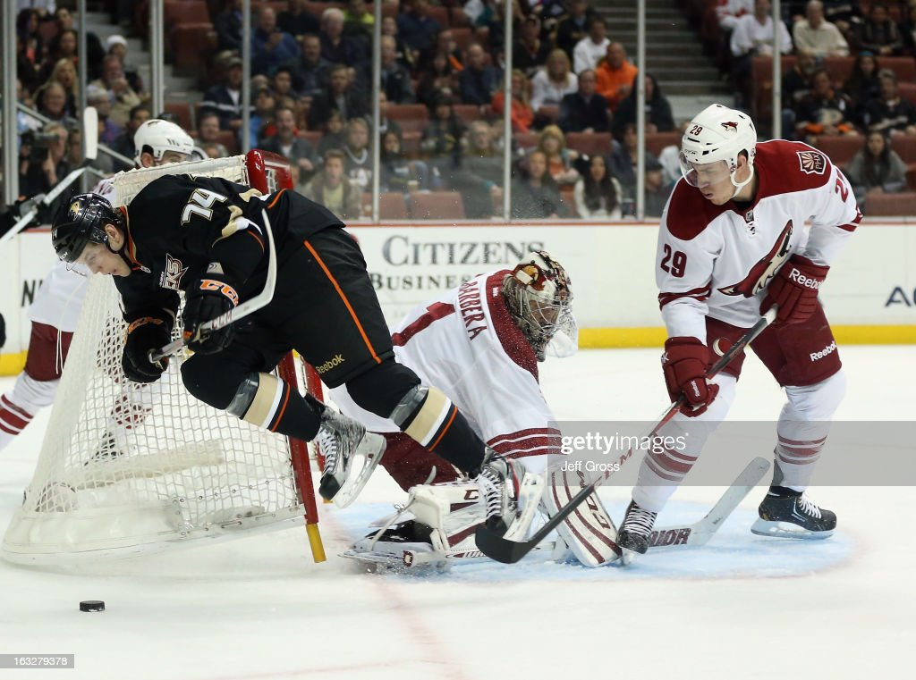 Peter Holland #74 of the Anaheim Ducks is tripped up by goaltender Jason LaBarbera #1 of the Phoenix Coyotes, as Michael Stone #29 of the Coyotes defends in the first period at Honda Center on March 6, 2013 in Anaheim, California.