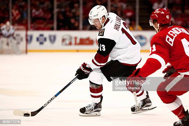 Peter Holland of the Arizona Coyotes looks to pass around Luke Glendening of the Detroit Red Wings during the third period at Joe Louis Arena on...