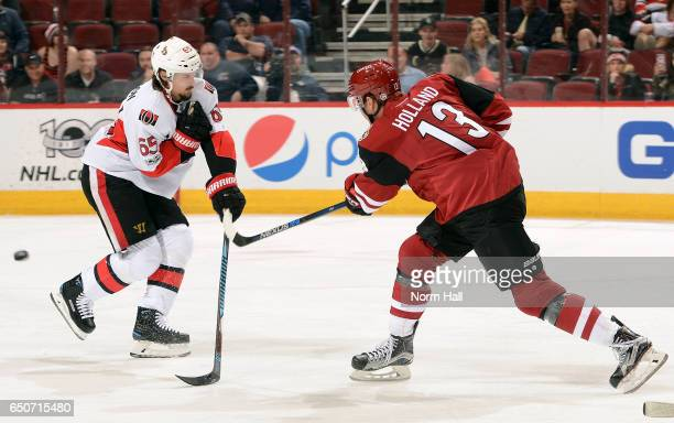 Peter Holland of the Arizona Coyotes shoots the puck past Erik Karlsson of the Ottawa Senators during the first period at Gila River Arena on March 9...