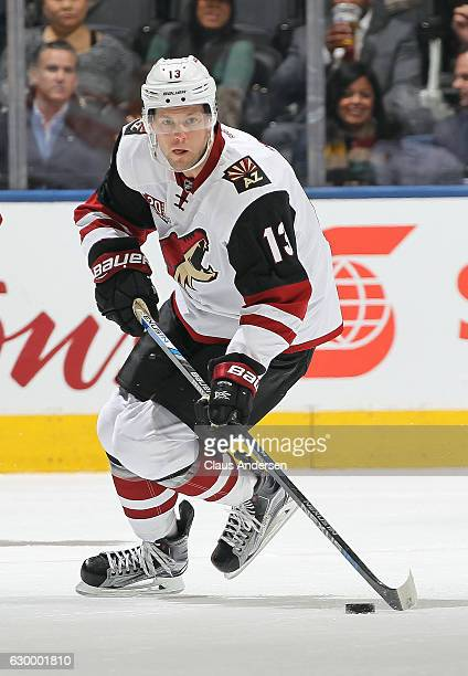 Peter Holland of the Arizona Coyotes skates up ice with the puck against the Toronto Maple Leafs during an NHL game at the Air Canada Centre on...