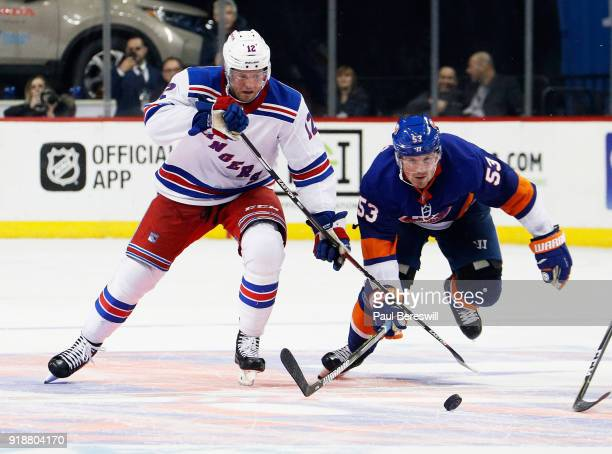 Peter Holland of the New York Rangers and Casey Cizikas of the New York Islanders chase down a loose puck during the third period at Barclays Center...