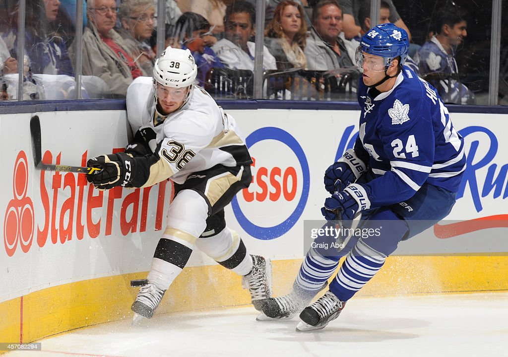 Peter Holland #24 of the Toronto Maple Leafs battles for the puck with Zach Sill #38 of the Pittsburgh Penguins during NHL game action October 11, 2014 at the Air Canada Centre in Toronto, Ontario, Canada.