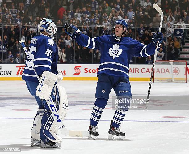 Peter Holland of the Toronto Maple Leafs congratulates teammate Jonathan Bernier after stopping the last shot in the shootout against the Buffalo...