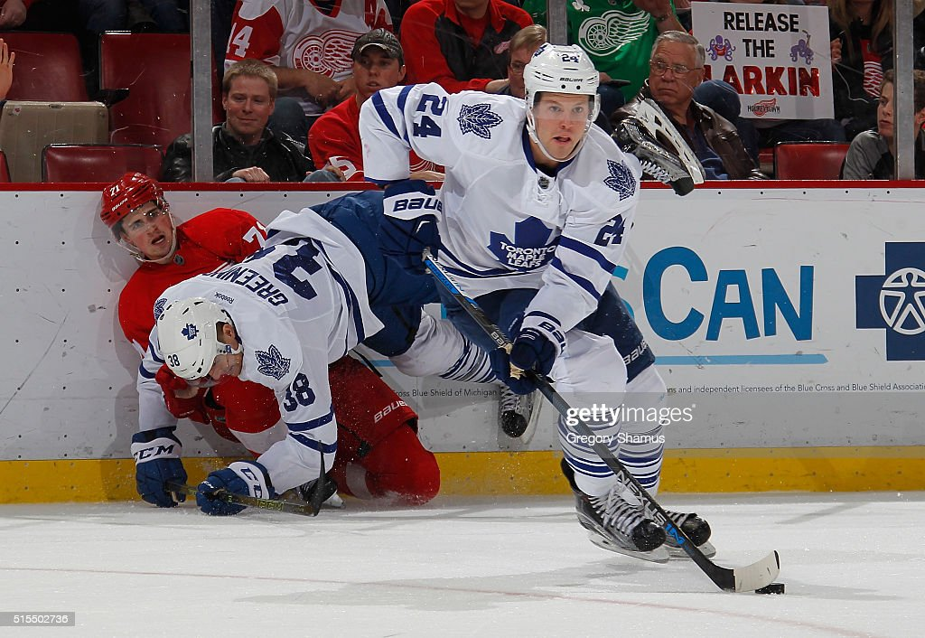 Peter Holland #24 of the Toronto Maple Leafs heads to the net with the puck after Dylan Larkin #71 of the Detroit Red Wings took a body check from Colin Greening #38 of the Maple Leafs during the third period at Joe Louis Arena on March 13, 2016 in Detroit, Michigan.