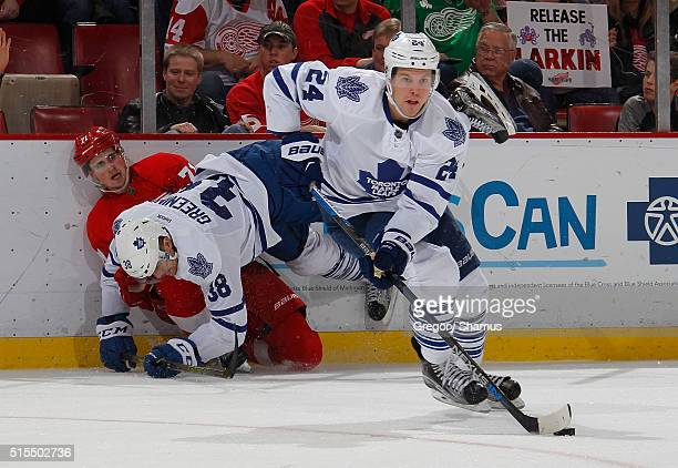 Peter Holland of the Toronto Maple Leafs heads to the net with the puck after Dylan Larkin of the Detroit Red Wings took a body check from Colin...
