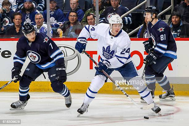 Peter Holland of the Toronto Maple Leafs plays the puck as Ben Chiarot of the Winnipeg Jets defends during third period action at the MTS Centre on...