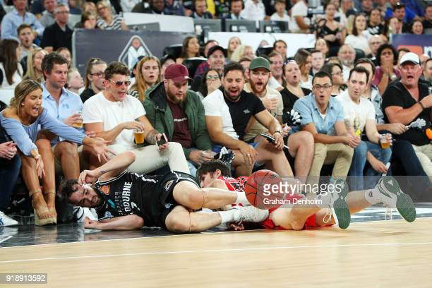 Peter Hooley of Melbourne United and Damian Martin of the Wildcats crash into the crowd during the round 19 NBL match between Melbourne United and...
