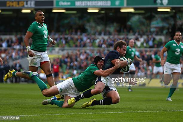 Peter Horne of Scotland scores his sides third try as Isaac Boss of Ireland attempts to hold him up during the International match between Ireland...