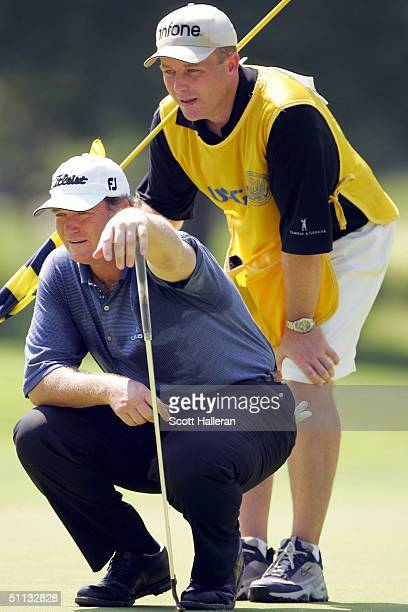 Peter Jacobsen and his caddie Mike O' Connell read a putt on the second green during the second round of the 25th US Senior Open on July 31 2004 at...
