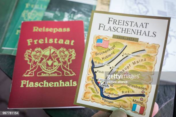 Peter Josef Bahles the president and founder of the Flaschenhals Free State Initiative holds a passport and a wine label introduced after the First...