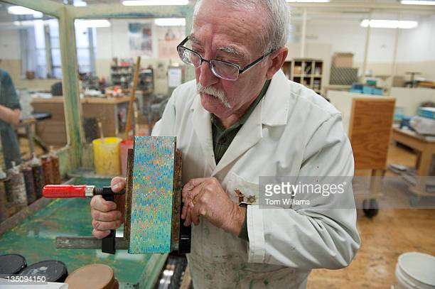 Peter K James Head Forwarder for the US Government Printing Office on North Capitol Street displays a recently marbled a book