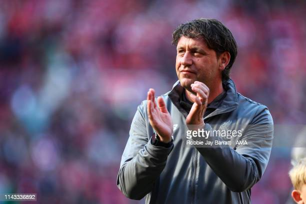 Peter Krawietz the assistant head coach / manager of Liverpool applauds the fans at full time during the Premier League match between Liverpool FC...