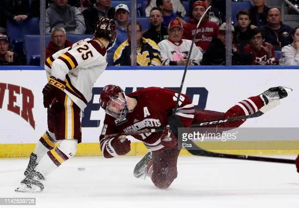 Peter Krieger of the Minnesota-Duluth Bulldogs filps Cale Makar of the Massachusetts Minutemen go after the puck during the 2019 NCAA Frozen Four the...