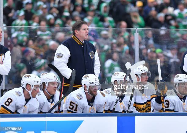 Peter Laviolette of the Nashville Predators watches the action from the bench during the 2020 NHL Winter Classic between the Nashville Predators and...
