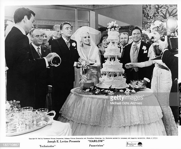 Peter Lawford and Carroll Baker cutting their wedding cake with Martin Balsam Red Buttons and Angela Lansbury watching in a scene from the film...