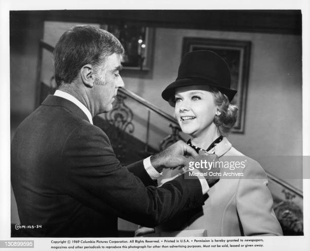Peter Lawford attaches ribbon to Anne Frances' coat in a scene from the film 'Hook Line and Sinker' 1969