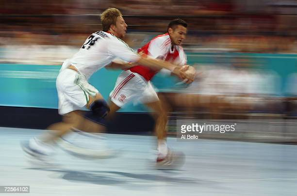 Peter Lendvay of Hungary attempts to strip the ball from Niksa Kaleb of Croatia in the men's handball classifications on August 27 2004 during the...