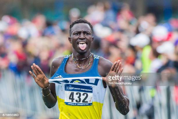 Peter Lomong of Northern Arizona University pops out his uniforms en route to the finish line during the Division I Men's Cross Country Championship...