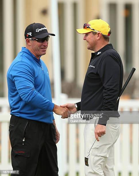 Peter Lonard of Australia and Jarrod Lyle of Australia shake hands during previews ahead of the 2013 Australian Masters at Royal Melbourne Golf...