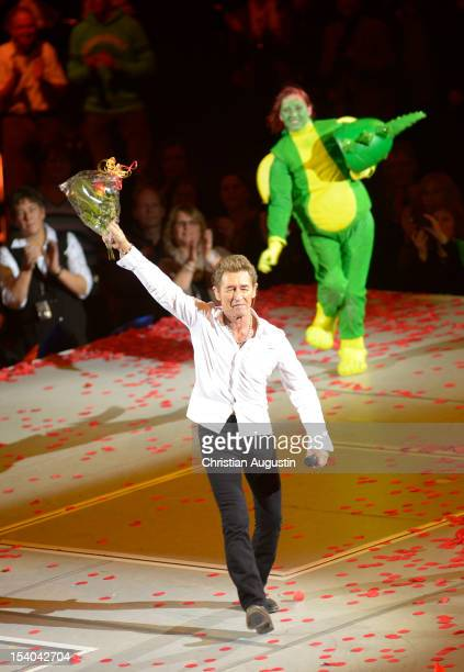 Peter Maffay and the dragon Tabaluga perform during the premiere of 'Tabaluga Und Die Zeichen Der Zeit' Premiere on October 12 2012 in Hamburg Germany