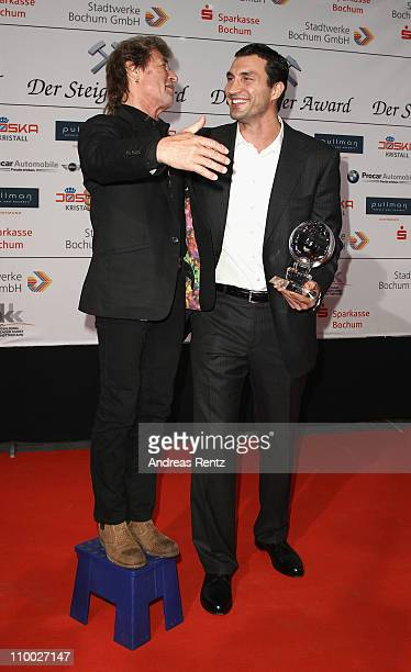 Peter Maffay stands on a stand as Vladimir Klitschko holds his award during the Steiger Award 2011 at the Jahrhunderhalle on March 12 2011 in Bochum...
