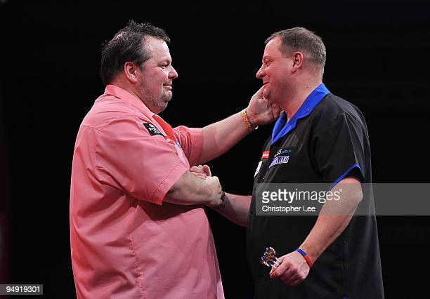 Peter Manley of England and Andy Jenkins of England shake hands after Manley wins during the 2010 Ladbrokescom World Darts Championship Round One at...
