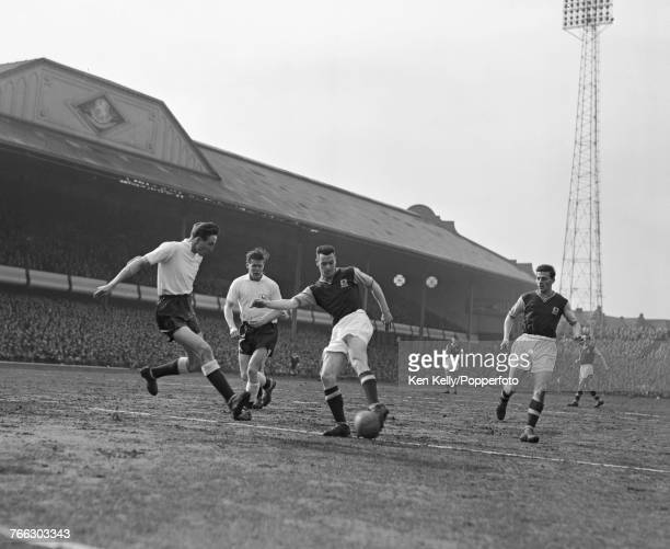 Peter McParland of Aston Villa pictured with the ball as Tottenham Hotspur defenders Mel Hopkins and Peter Baker move in for a tackle during play...