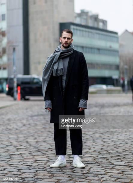 Peter Moestl wearing a black coat grey scarf black pants white sneaker at the Copenhagen Fashion Week Autumn/Winter 17 on February 1 2017 in...