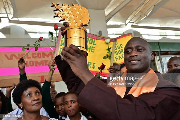 Peter Mokaya Tabichi winner of the renowned Global Teacher's Prize holds up his trophy on March 27 2019 upon arrival at Nairobi's Jomo Kenyatta...