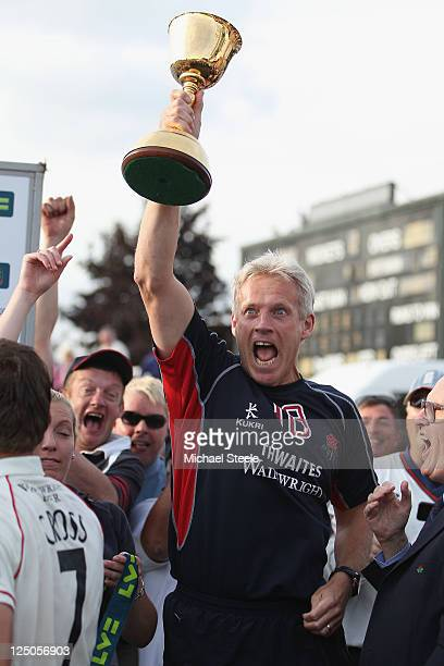 Peter Moores Head Coach of Lancashire lifts the Championship trophy after his sides eight wicket victory during the LV County Championship match...