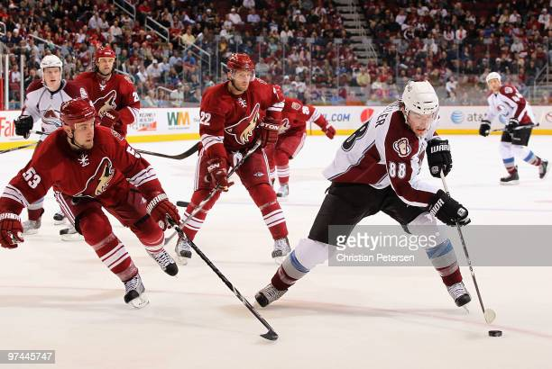 Peter Mueller of the Colorado Avalanche skates with the puck past Derek Morris and Lee Stempniak of the Phoenix Coyotes during the third period of...