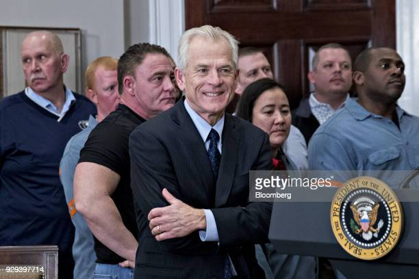 Peter Navarro director of the National Trade Council center stands next to to steel and aluminum workers after US President Donald Trump not pictured...