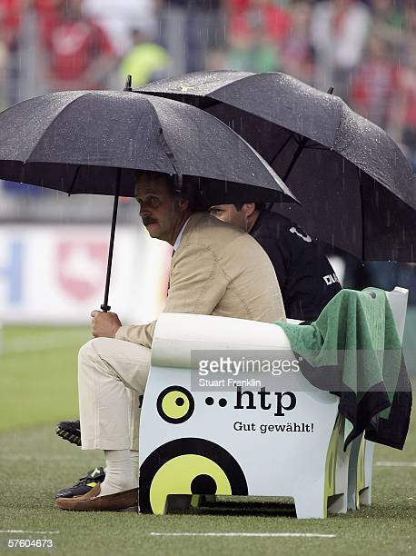 Peter Neururer, Trainer of Hanover 96 shelters under an umbrella during the thunder storm during the Bundesliga match between Hanover 96 and Bayer...
