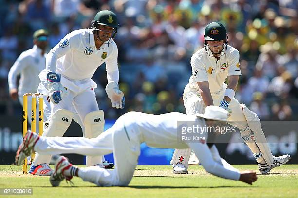 Peter Nevill of Australia looks on as Hashim Amla of South Africa takes a catch during day two of the First Test match between Australia and South...