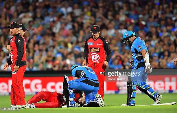 Peter Nevill of the Melbourne Renegades lays on the ground after being struck in the head by the bat of Brad Hodge of the Adelaide Strikers as Jono...