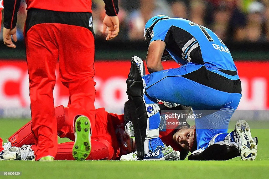 Peter Nevill of the Melbourne Renegades lays on the ground after being struck in the head by the bat of Brad Hodge of the Adelaide Strikers as Jono Dean of the Adelaide Strikers attends to him during the Big Bash League match between the Adelaide Strikers and the Melbourne Renegades at Adelaide Oval on January 16, 2017 in Adelaide, Australia.