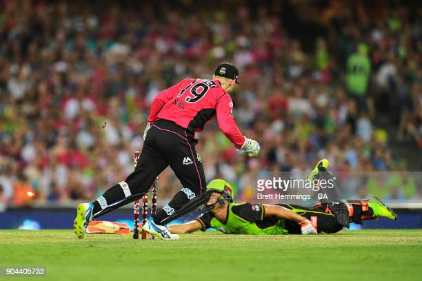 Peter Nevill of the Sixers runs out Chris Green of the Thunder during the Big Bash League match between the Sydney Sixers and the Sydney Thunder at...